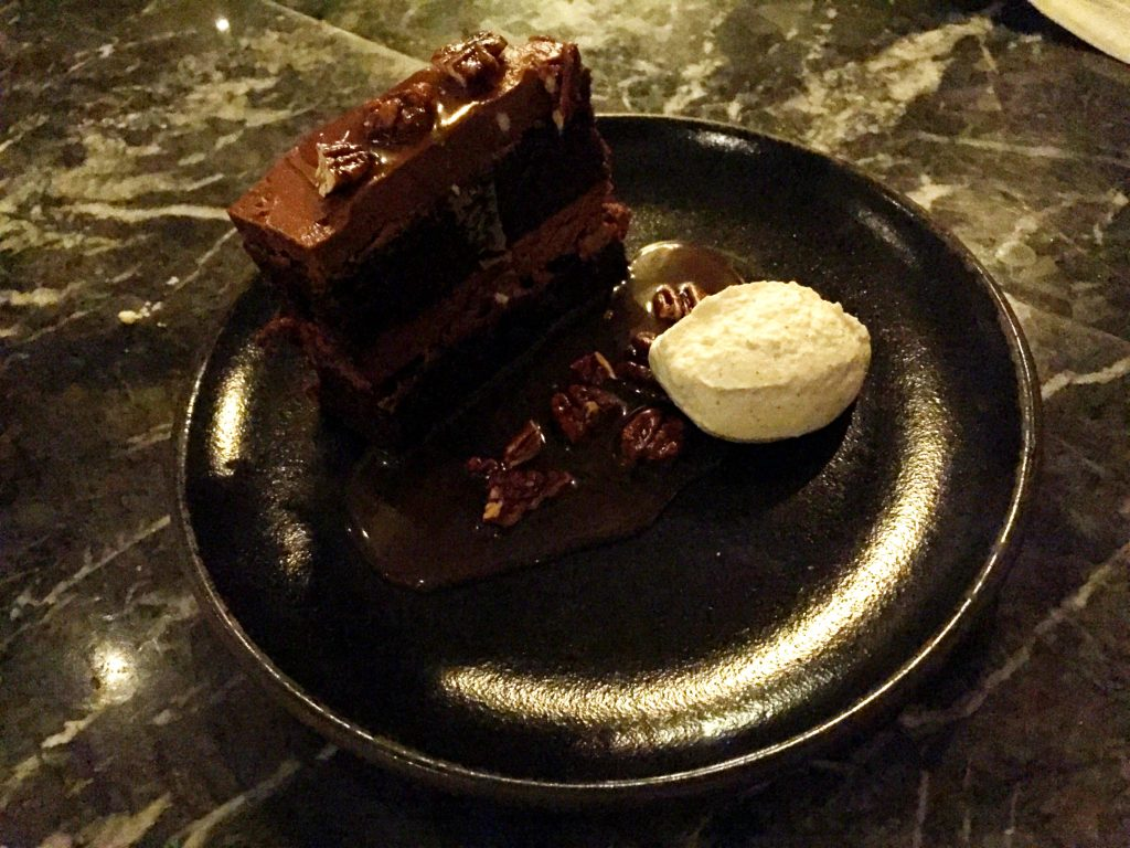 chocolate cake with salted caramel, candied pecans and whipped cream at Norah restaurant Los Angeles
